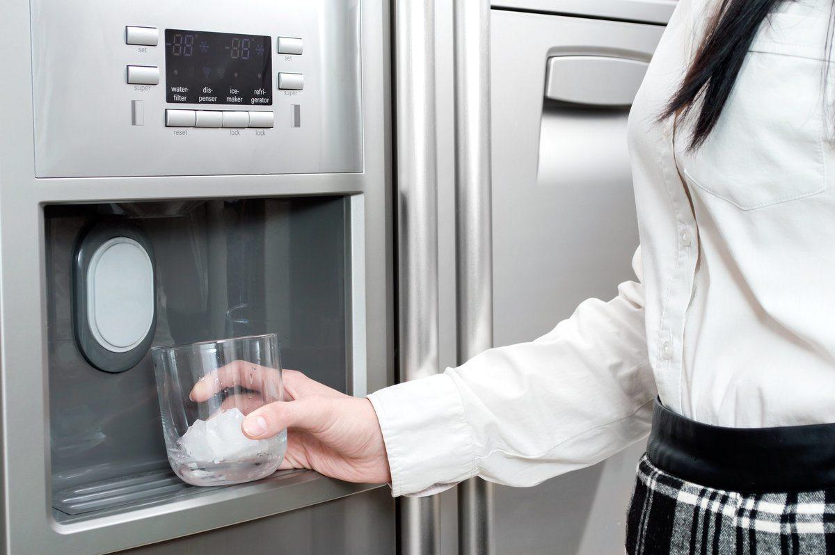 زنی در حال آب ریختن از یخچال
