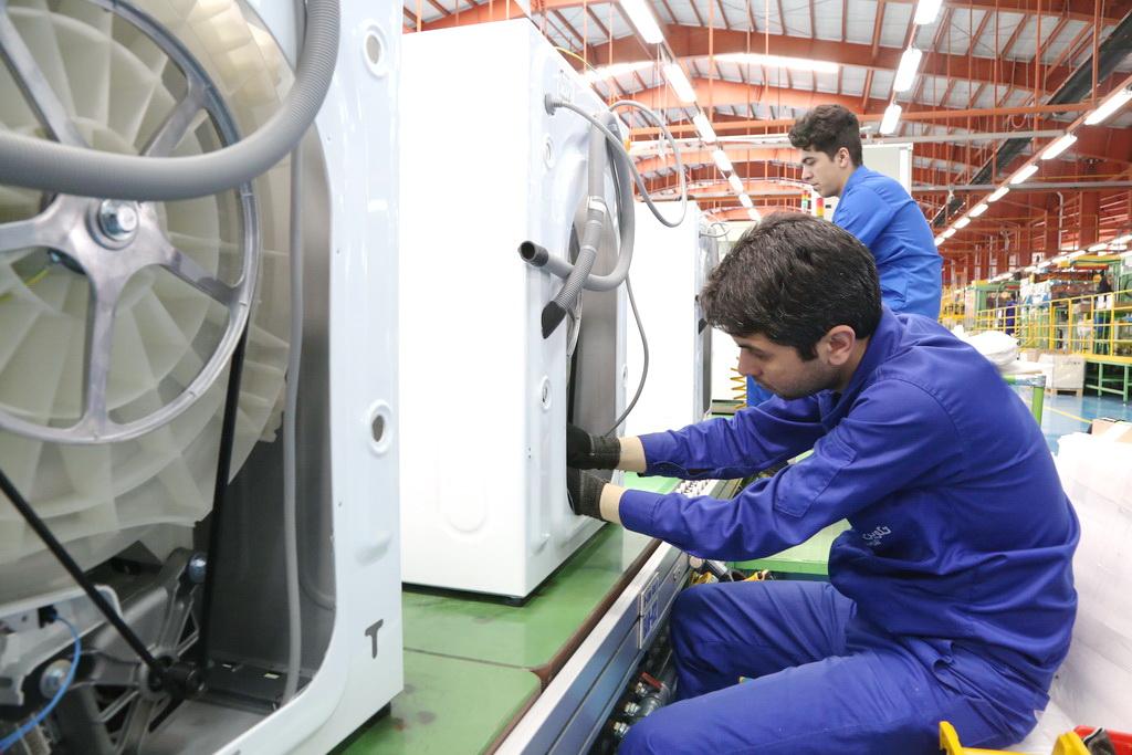 مردان در حال کار در خط تولید ماشین لباسشویی