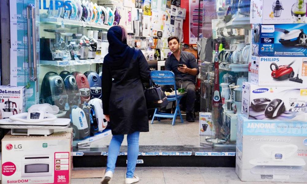 فروشنده فروشگاه لوازم خانگی در حال صحبت با خریدار